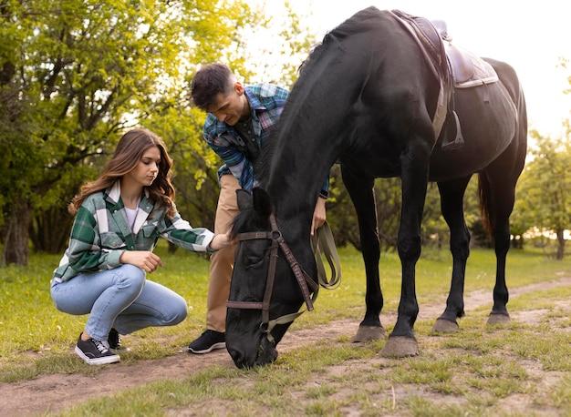 フルショットのカップルと馬