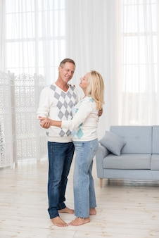Full shot couple dancing in the living room
