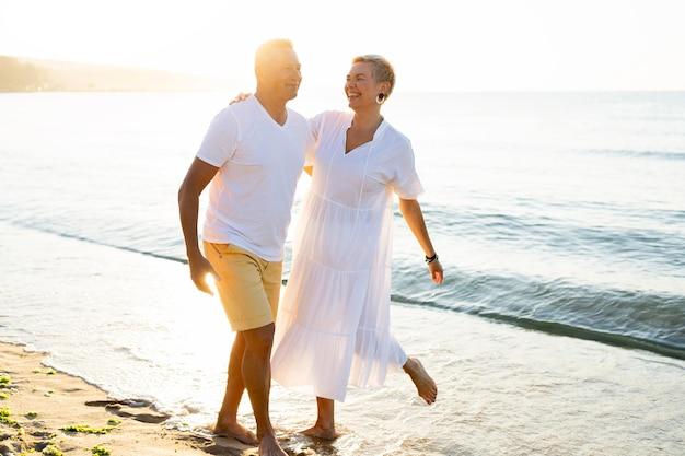 Полный снимок пара, развлекающаяся на берегу моря