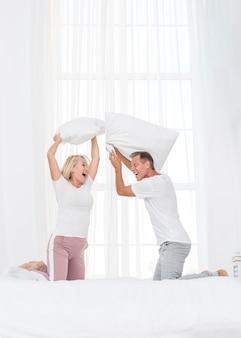 Full shot couple having a pillow fight