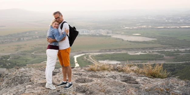 Full shot couple hugging on cliff