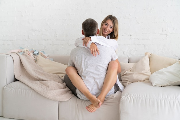 Full shot couple hugging on the couch