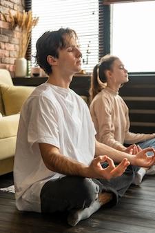 Полный снимок пара, медитирующая вместе