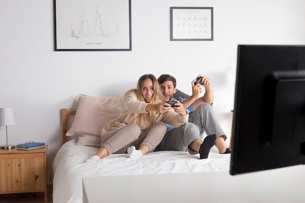 ベッドでビデオゲームをプレイするフルショットのカップル