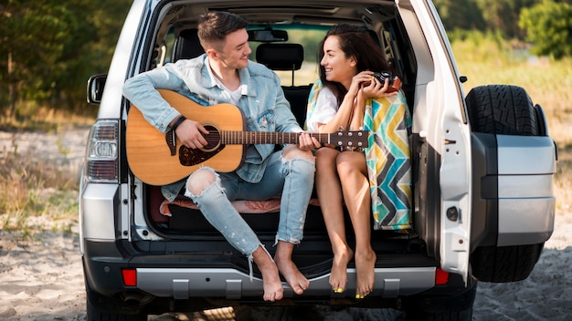 トランクに座っているフルショットのカップル