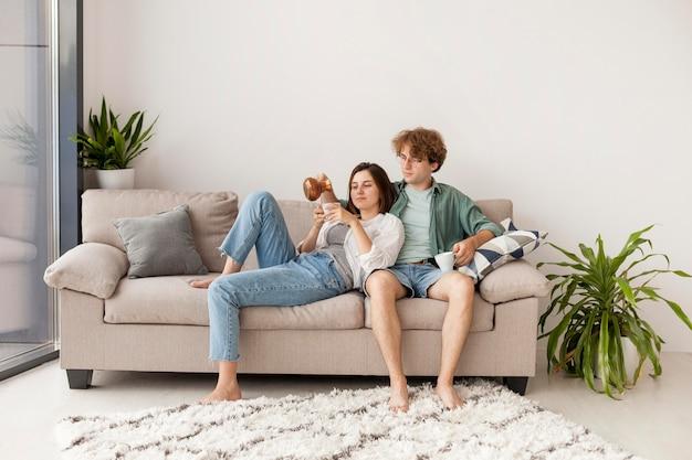 Пара полный выстрел, сидя на диване