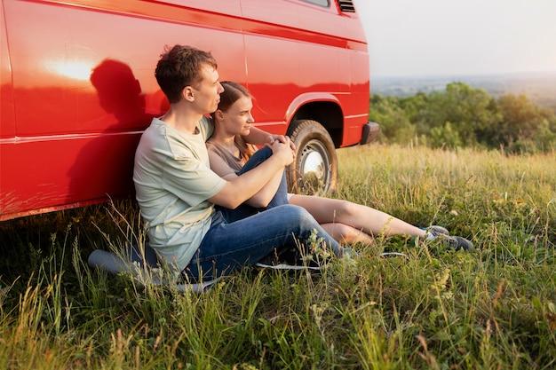 草の上に座っているフルショットのカップル