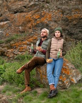 Пара в полный рост, сидя на скале и выпивая