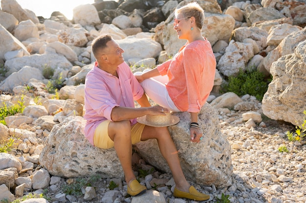 Пара в полный рост, сидя на скалах