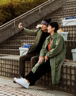 自撮り写真を撮るフルショットカップル