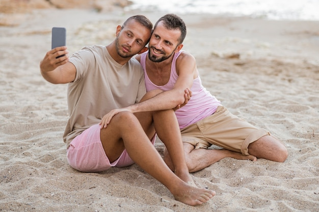Full shot couple taking selfies on beach