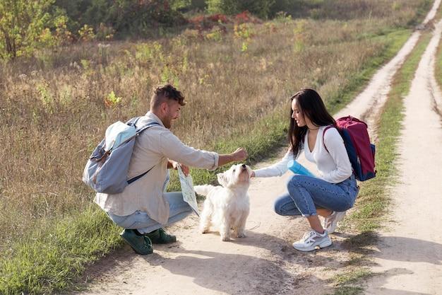 犬と一緒に旅行するフルショットのカップル