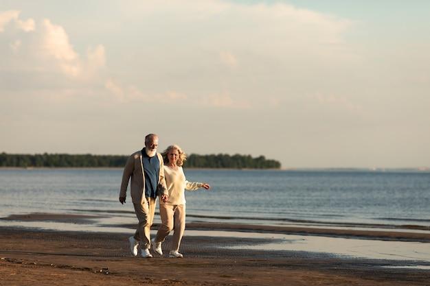 ビーチで歩くフルショットカップル