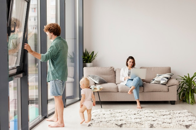 Full shot couple with baby in living room