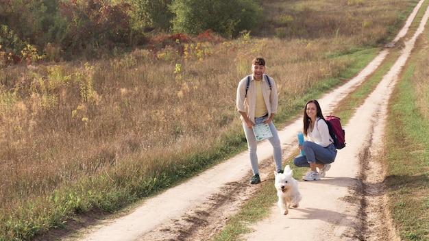 시골에서 강아지와 함께 전체 샷된 커플