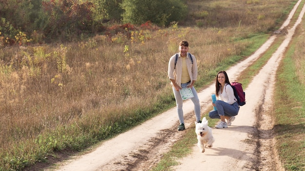 Full shot couple with dog at countryside