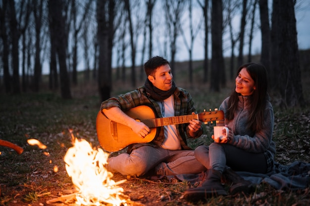 Full shot couple with guitar
