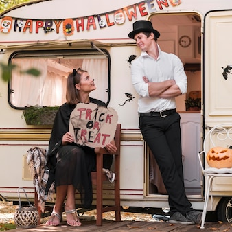 Full shot couple with trick or treat sign