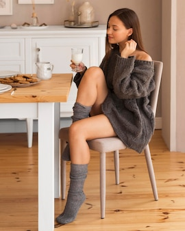 Full shot cozy woman on chair holding glass of milk