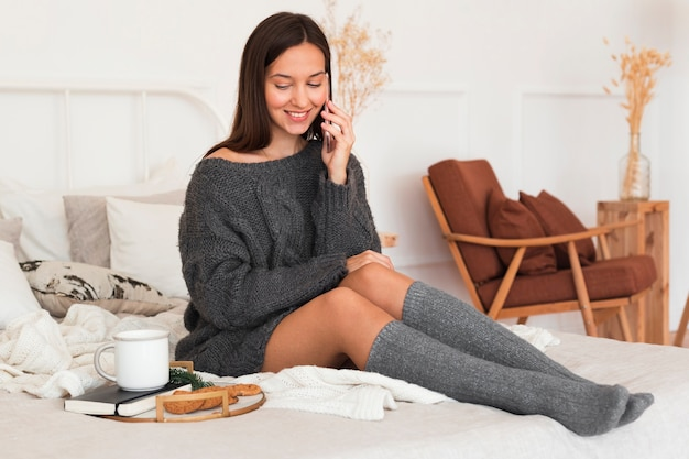 Full shot cozy woman sitting on bed with milk, cookies and agenda