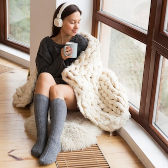 Full shot cozy woman with blanket and mug