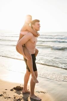 ビーチでフルショットのかわいいカップル