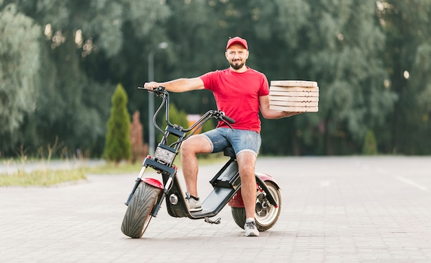 Full shot delivery guy on motorcycle with order