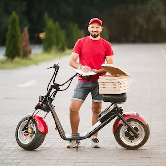Full shot delivery guy posing outdoors