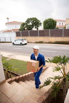 Full shot delivery man carrying box