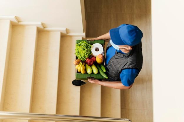 Полный доставщик поднимается по лестнице