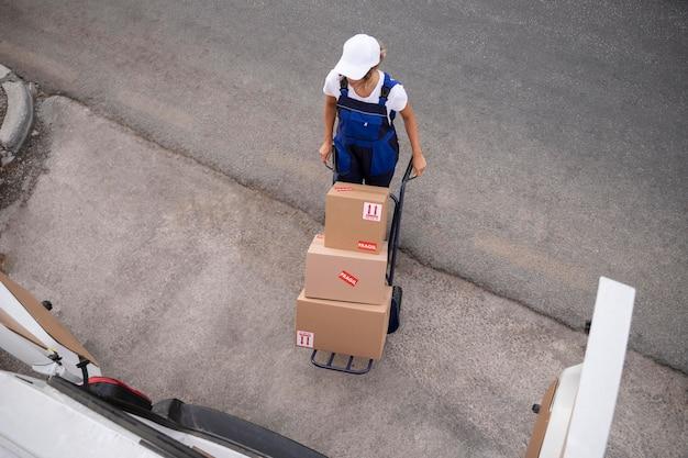 箱を運ぶフルショット配達の女性