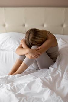 침대에서 전체 샷 우울한 여자