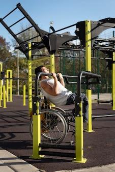 Uomo disabile del colpo pieno che fa sport nel parco