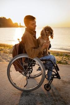 Full shot disabled man holding dog