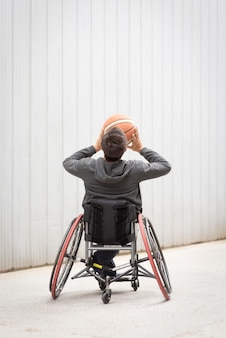 Full shot disabled man playing basketball