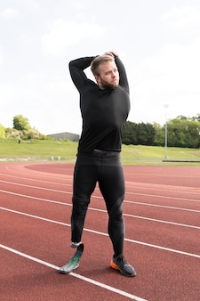 Full shot disabled man stretching on running track