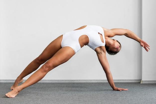 Full shot exercising in gymnast suit