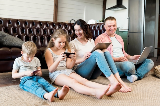 Famiglia della foto a figura intera che pone sul pavimento