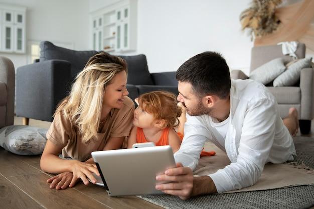 Полная семья, лежа на полу с планшетом