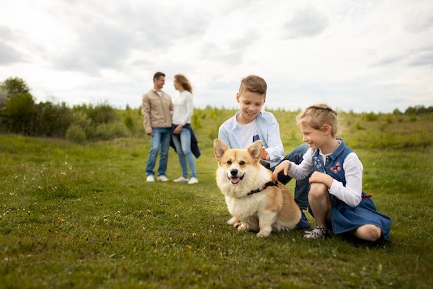 Full shot family playing with dog outdoors