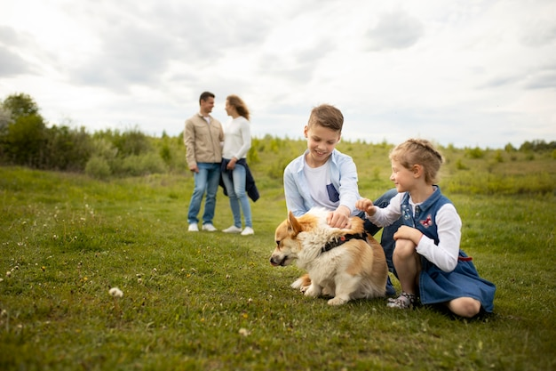Full shot family playing with dog