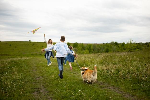 屋外で凧で遊ぶフルショット家族