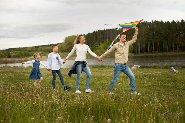 Full shot family playing with rainbow kite