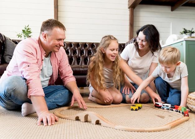Famiglia della foto a figura intera che gioca con il treno