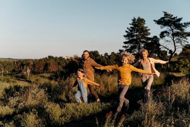 Full shot family running on meadow
