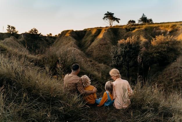 Full shot family sitting on grass