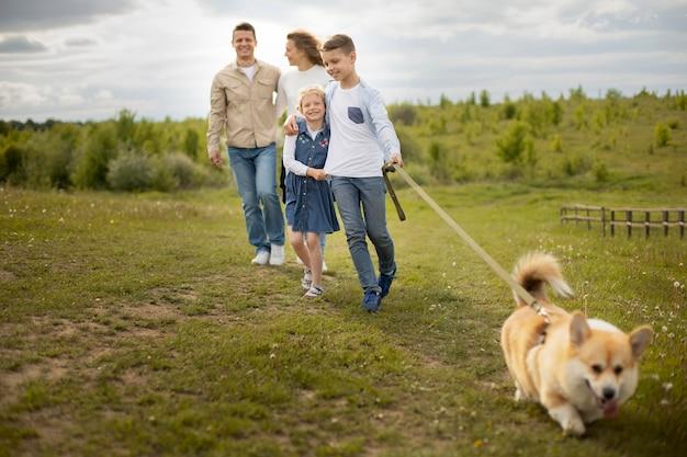 Полная семья выгуливает собаку