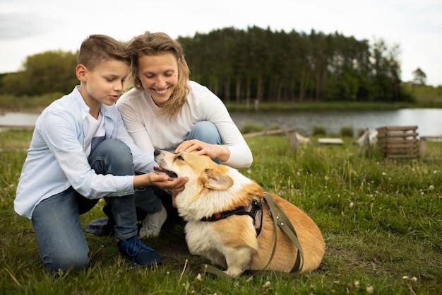 Famiglia a tutto campo con un simpatico cane in natura