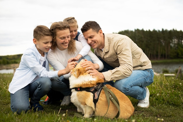 Full shot family with cute dog outside