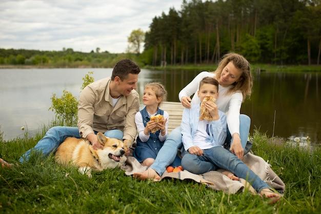 屋外で犬とフルショット家族